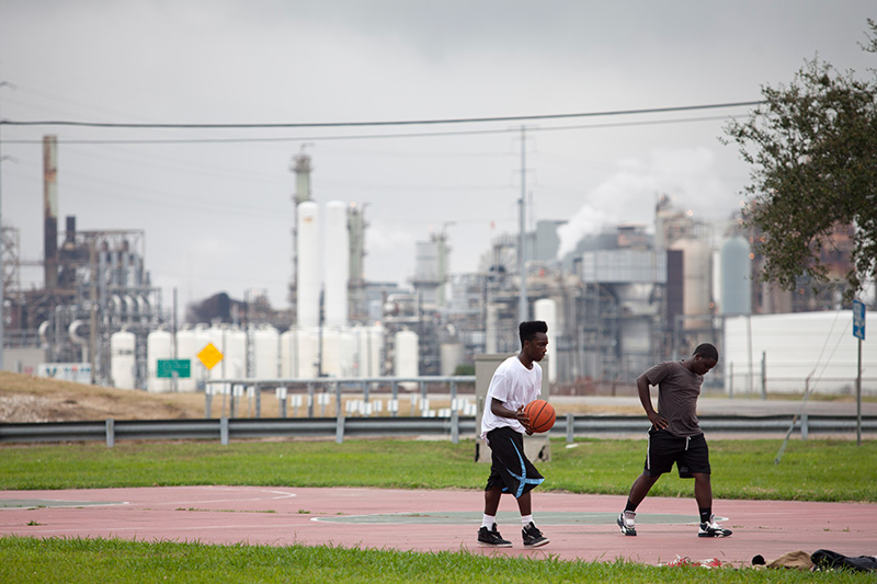 Teenagers play basketball in the Carver Terrace housing project in Port Arthur, TX, in the shadow of an oil refinery.