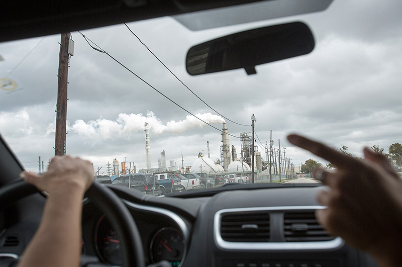 Photo of a polluting oil refinery through the windshield a car leading a toxic tour.