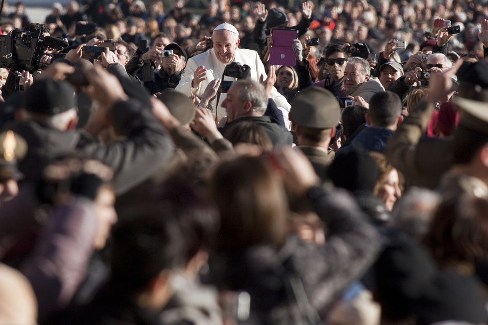 Pope Francis surrounded by the crowd in Vatican City.