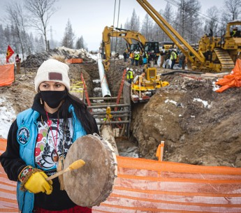Gio Cerise, a member of the White Earth Nation, plays a drum and prays in front of Line 3 pipeline construction on Highway 169 south of Hill City, Minn.