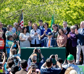 Gov. Jay Inslee signs a bill that establishes a 100% clean energy target for Washington state.