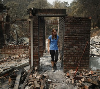 Emily Scott walks through the ruins of her house burned in the July 2018 Carr Fire in Shasta, CA. Climate change is making wildfires more ferocious.