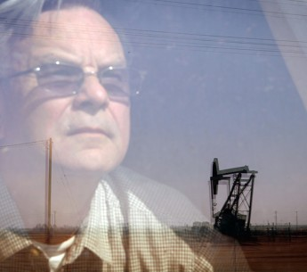 Walt Desatoff looks out window at oil field across the street