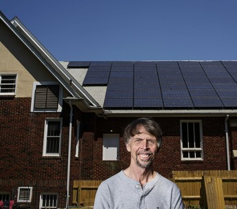 David Brosch stands in front of a 22 kilowatt solar electric array atop the roof of the University Park Church of the Brethren in Maryland.