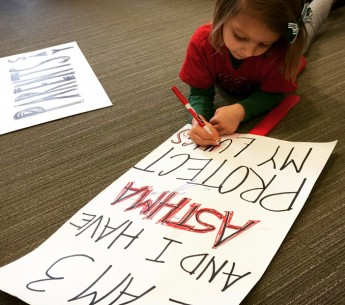 "Fiona helps prepare a sign that reads ""I am 3 years old and I have asthma. Protect my lungs."""