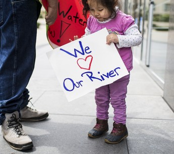Yurok Tribe members Tseeyaba Kinney, 2, and her father, Isaac, rally outside the Burton Federal Building in San Francisco on Apr. 10, 2018.