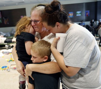 Leigh Bolding, center, cries with her daughter Kayla Cromer, right, as she holds her grandchildren at an evacuation shelter in the aftermath of Hurricane Michael. Extreme weather fueled by climate change threatens communities across the United States.