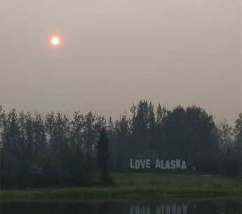 Smoke obscures the sun along the Chena River in Fairbanks on July 8, 2019. Record high temperatures in Alaska in early July worsened wildfires burning throughout the state.