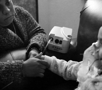 A mother watches over her child during treatment for asthma.