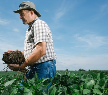 Chris Teachout, a fifth-generation farmer, examines the quality of his soil, which he keeps healthy by planting cover crops on his farm in southwest Iowa.