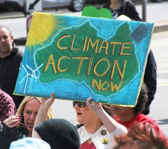 """Photo of an Australian woman holding a protest sign reading, """"Climate Action Now."""""""