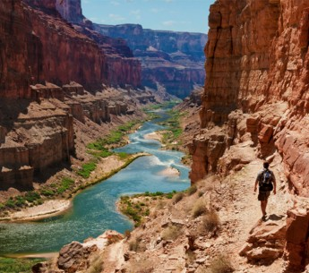 A hiker walks along the Colorado River.