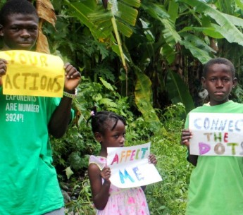 Children in Haiti hold up signs urging the international community to take action on climate change.