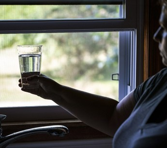Barbara Deardorff draws water from her tap in Wheatfield, Indiana, where toxic chemicals from a local coal ash pond have leached into her community's water supply.
