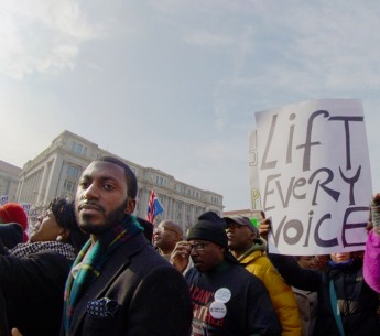 Black community members speak out against racism at the 2014 Justice for All march in Washington, D.C. From housing to education and from health care to environmental justice, Trump seeks to set our communities back.