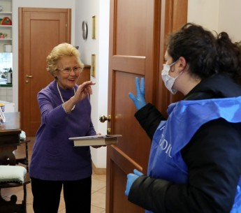 A volunteer speaks to a woman she's providing with home care in Rome during Italy's COVID-19 lockdown.