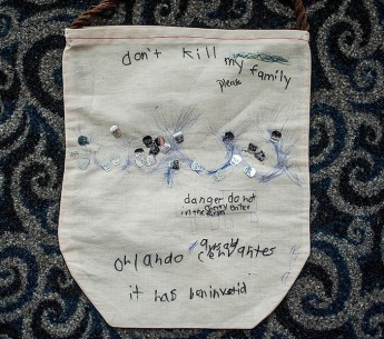 """A bag made by the child of a farmworker. The bag, embroidered with the words """"Don't kill my family please,"""" is adorned with skulls. It was presented to Sen. Charles Shumer's office by farmworkers and advocates, who had traveled to Washington, D.C. in July"""