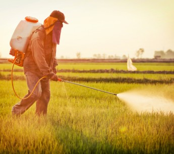 A farmer spraying a field with pesticides.