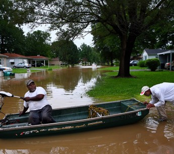 Danny Lane, right, gives his friend Walter Byrd a push as Byrd prepares to head down a flooded Centreville street in June 2015. Firefighters evacuated residents earlier in the day.