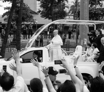 A crowd waves to Pope Francis.