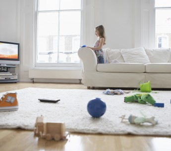 girl on couch with toys on floor