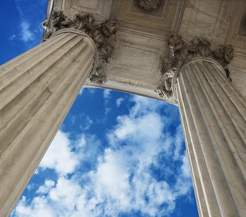 Supreme Court columns reach up toward a blue sky.