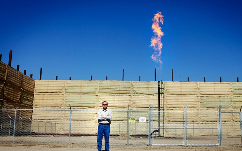 Walt Desatoff in front of oil rig in Shafter, CA