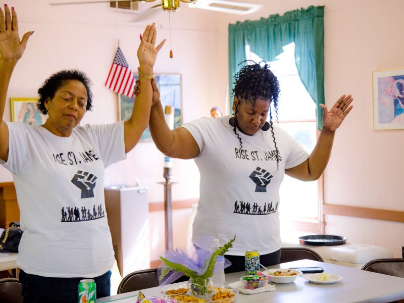 Sharon Lavigne (left), founder of RISE St. James, joins another activist in a moment of prayer at a community meeting in 2019.