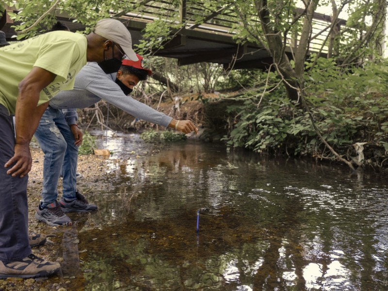 Dennis Chestnut teaches his grandson, Horus Plaza, how to test the water quality of the Watts Branch of the Anacostia River in Marvin Gaye Park in Washington, D.C. in May 2021.