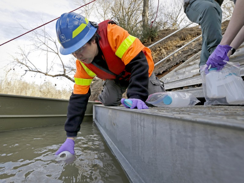 An EPA contractor collects a water sample from the site of a coal ash spill on the Dan River in North Carolina.