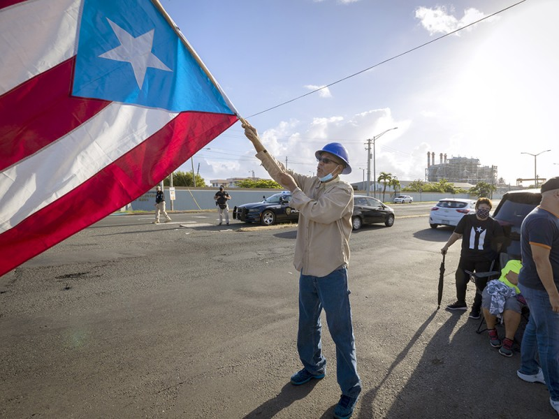 A protester waves the Puerto Rican flag during a public protest against the privatization of the electric power service in San Juan, Puerto Rico, in June 2021.