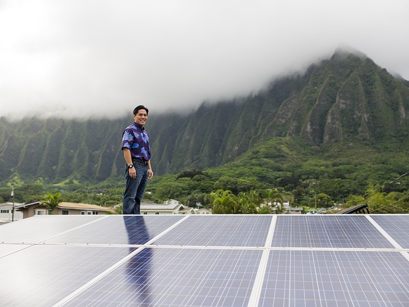 Earthjustice managing attorney Isaac Moriwake stands on his O'ahu rooftop, which has been retrofitted with solar panels.