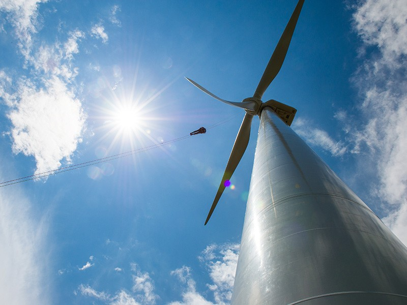 A technician repels down the blades of a wind turbine in Colorado during an inspection.