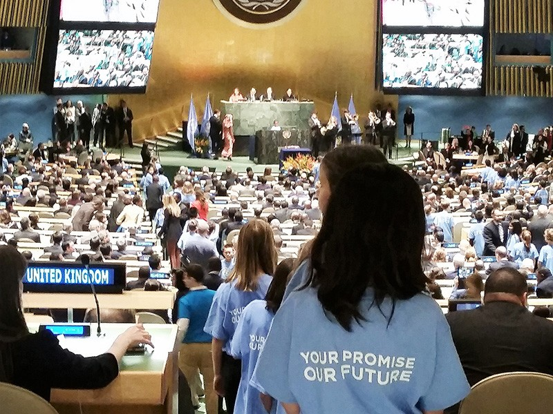 """Schoolchildren, all wearing shirts with the words: """"Your Promise, Our Future,"""" streamed down the aisles at the close of the Paris Agreement signing ceremony at the UN General Assembly in New York, April 22, 2016."""