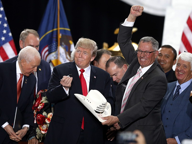 President Donald Trump signs the hat of Bruce Adams, chairman of the San Juan County Commission, after signing a proclamation to shrink the size of Bears Ears and Grand Staircase Escalante national monuments.