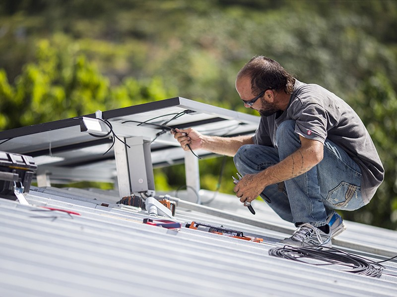 A technician installs a solar energy system at a home in Adjuntas, Puerto Rico, in July 2018. The island is part of a growing list of U.S. states and cities that have committed to 100% clean energy.