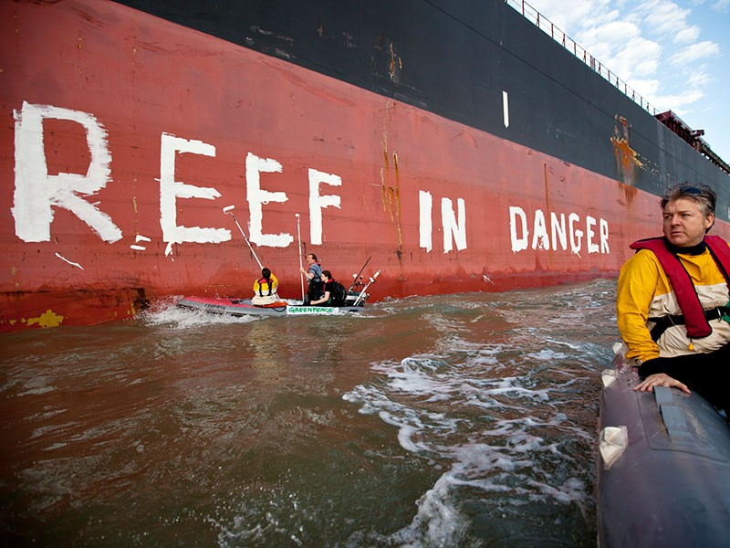 """Activists paint the message """"Reef in Danger"""" on the side of a coal ship in Gladstone, Australia, in 2012."""
