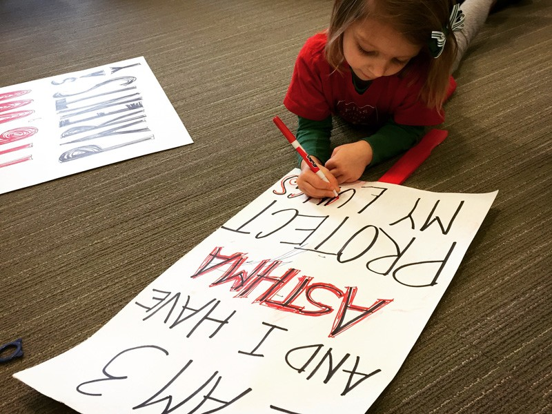 """Fiona helps prepare a sign that reads """"I am 3 years old and I have asthma. Protect my lungs."""""""