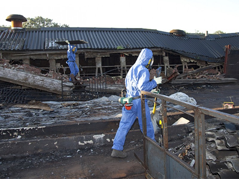 Workers wear protective gear as they remove asbestos, one of the substances regulated under the Toxic Substances Control Act.