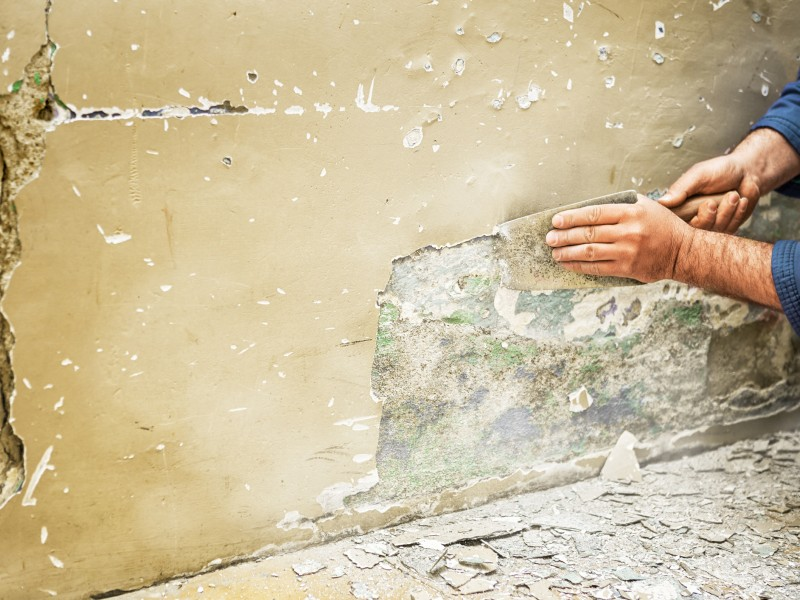 A worker scrapes old paint off a wall.