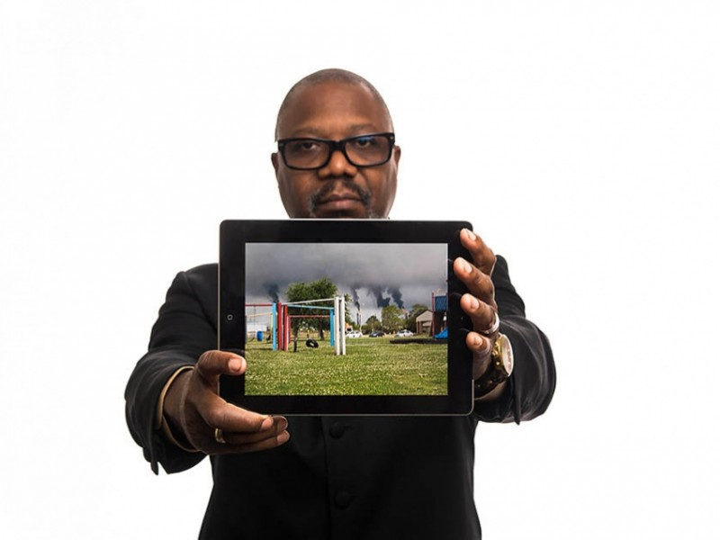 """Hilton Kelley holds an image of an oil refinery """"flaring"""" near a community playground in Port Arthur, Texas."""
