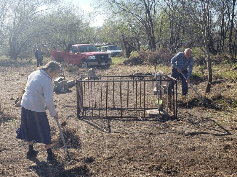 Mr. and Mrs. Villarreal tending the grounds at the Eli Jackson Ranch Church and Cemetery.