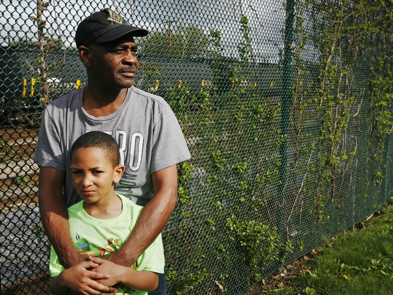 Be Be White and his son Brayton, six years old, stand along the fence that separates the railroad tracks with cars containing hazardous crude oil from Ezra Prentice Homes.
