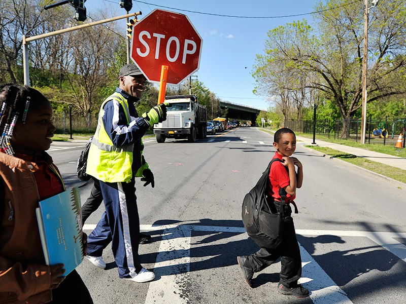 School crossing guard Be Be White stops traffic on South Pearl Street for children, including his son Brayton and Sanaiya, both six years old. White, who has lived in Ezra Prentice Homes for 12 years is among the residents who attended meetings against th