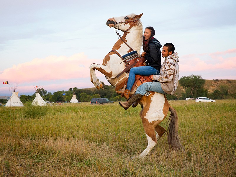 Stevana Salazar (left) of the Kickapoo Tribe of Texas rides with Arlo Standing Bear, Oglala Lakota from Allen, S.D., in the Sacred Stone Camp, Aug. 26, 2016.