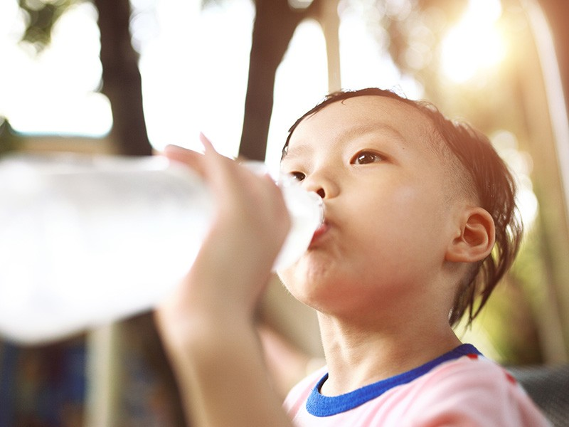 A boy drinks water.