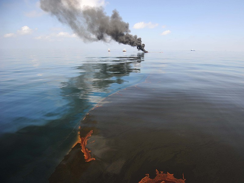 Dark clouds of smoke and fire rise from a controlled oil fire in the Gulf of Mexico following the April 20, 2010, explosion on the Deepwater Horizon.