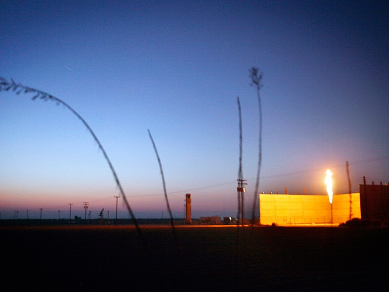 As the sun sets on another California day, a flare burns in an oil field near Bakersfield, CA.