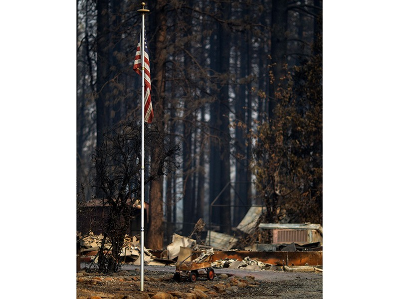 A U.S. flag remains standing in a Paradise, California, neighborhood, Nov. 17, 2018, days after the Camp Fire overran the town.