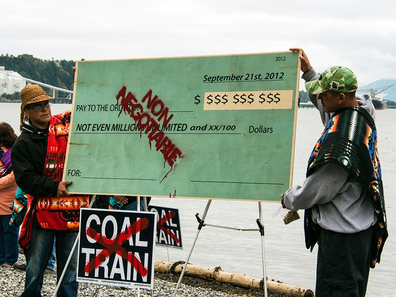 Lummi members hold a symbolic check burning protest to demonstrate that no amount of money can buy their support.